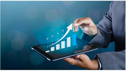 A personal holding a tablet indicating a graph on business growth